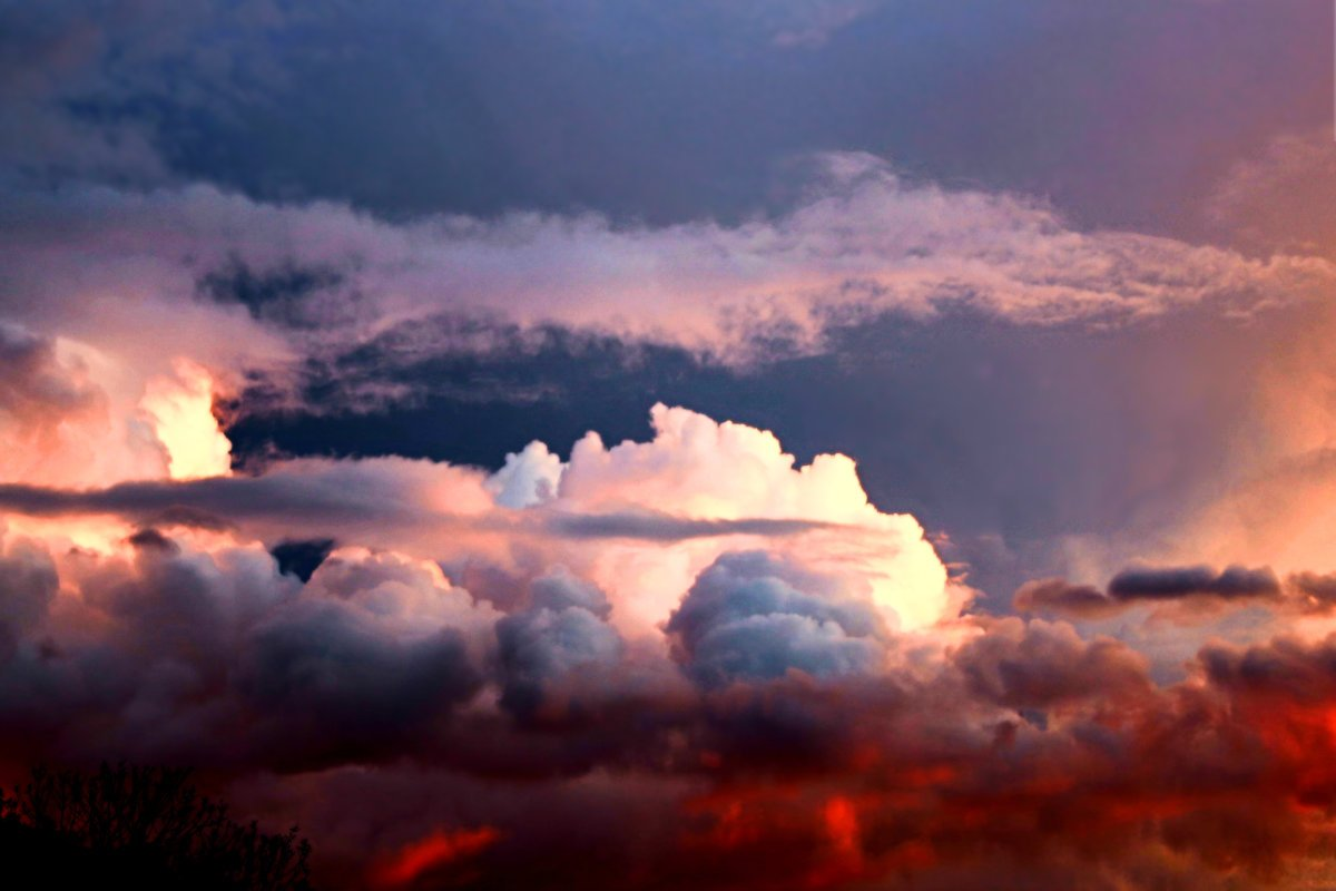 Colorful thunderstorm at sunset. Clouds are deep red, glowing white, dark blue, lavender purple, vibrant orange sky. Photo from San Francisco Bay Area.