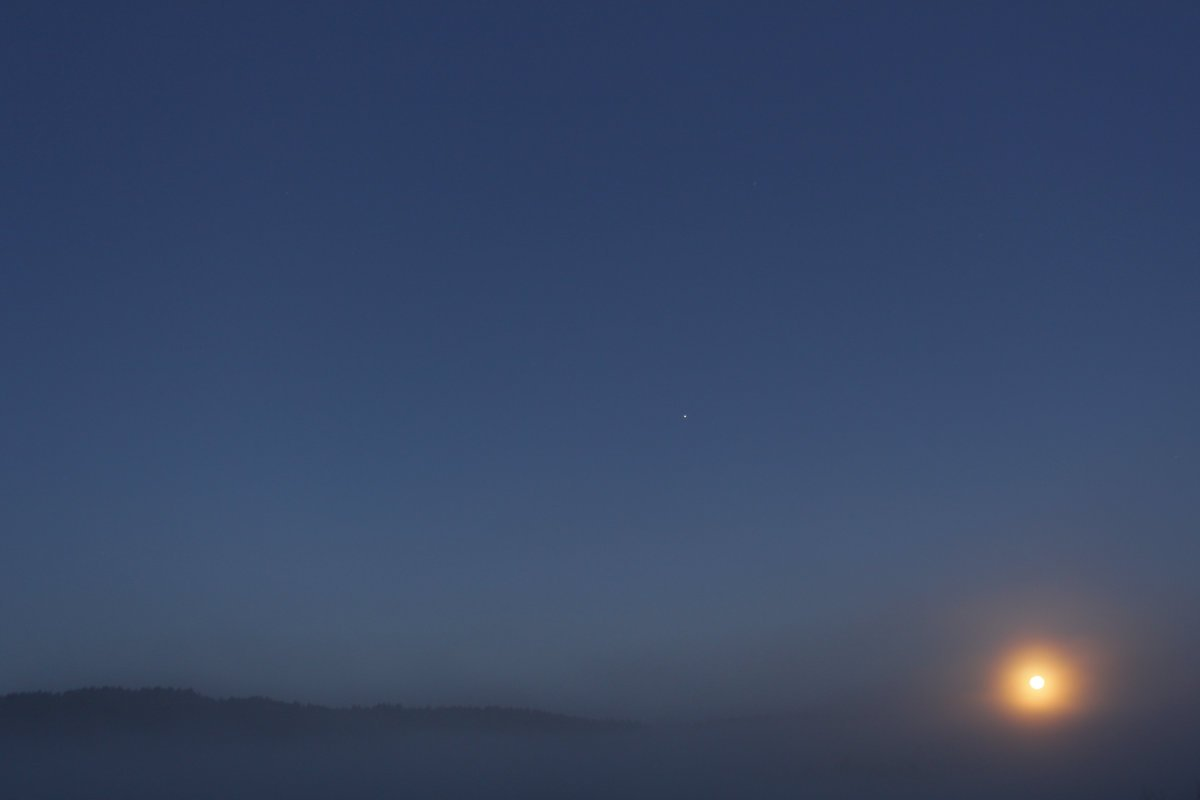 A mystical astronomical photo taken from Earth. Evening sky with glowing orange moon orb on the horizon visible through fog. Clear sky above with Jupiter visible. Mountain ridge in distance low on horizon. Photo taken in Mendocino County, California.