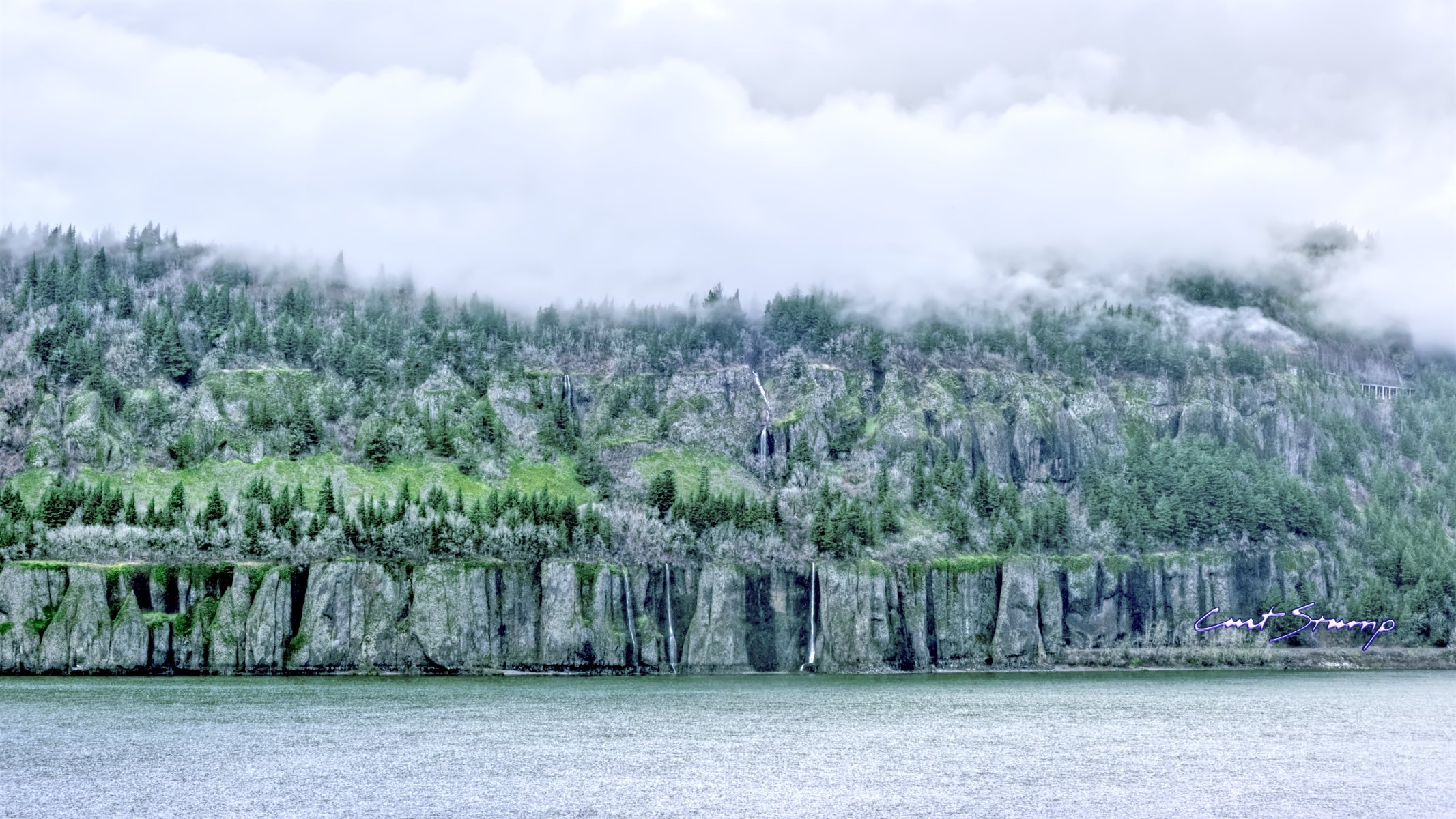 Photo of the Columbia River Gorge taken from the Oregon side, looking to the Washington side. Picture of river, rock cliffs, waterfalls, road bridge, evergreen trees touching the clouds.
