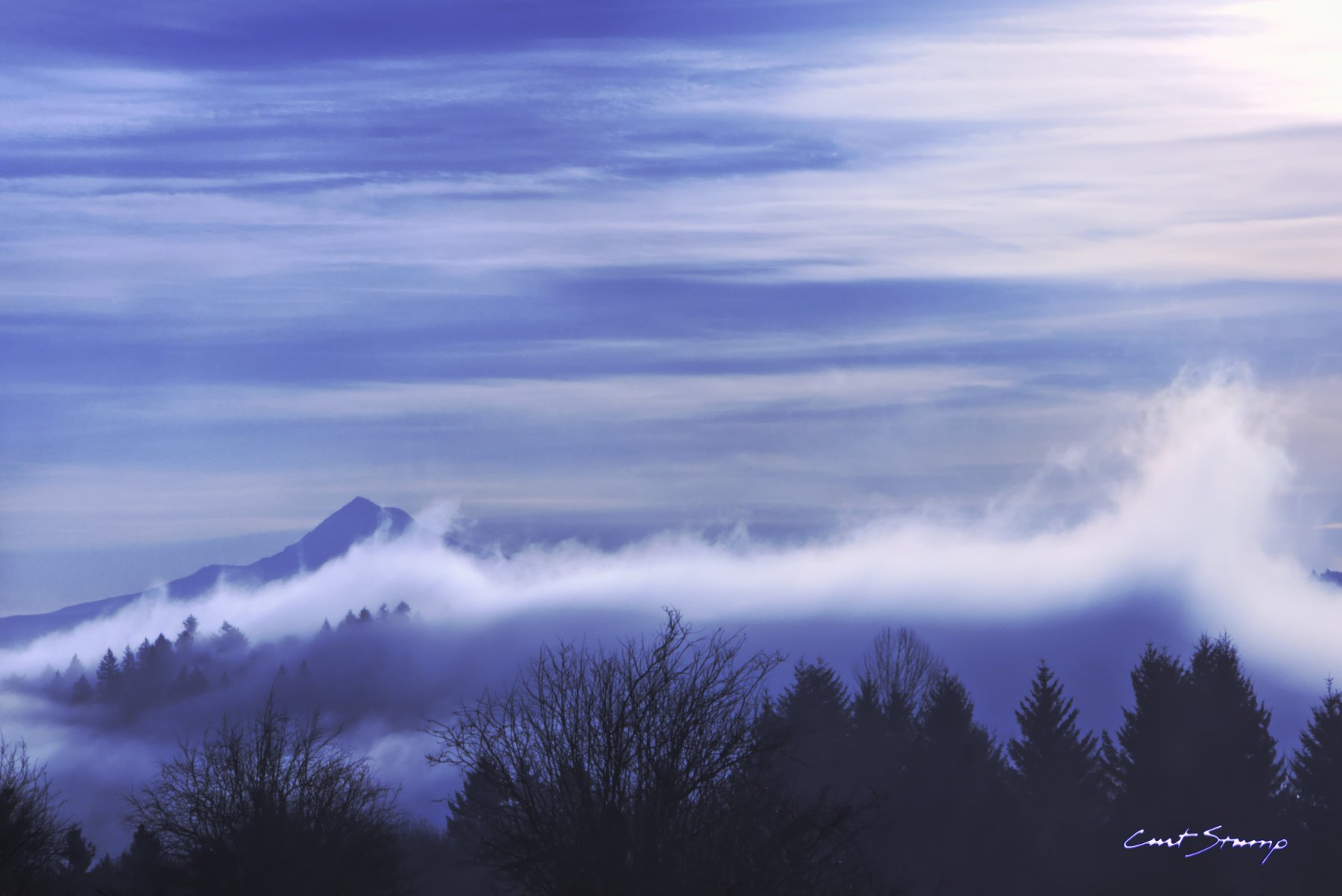 View of Mount Hood, Oregon, in the distance with fog in foreground with trees. Streaked clouds and blue sky.