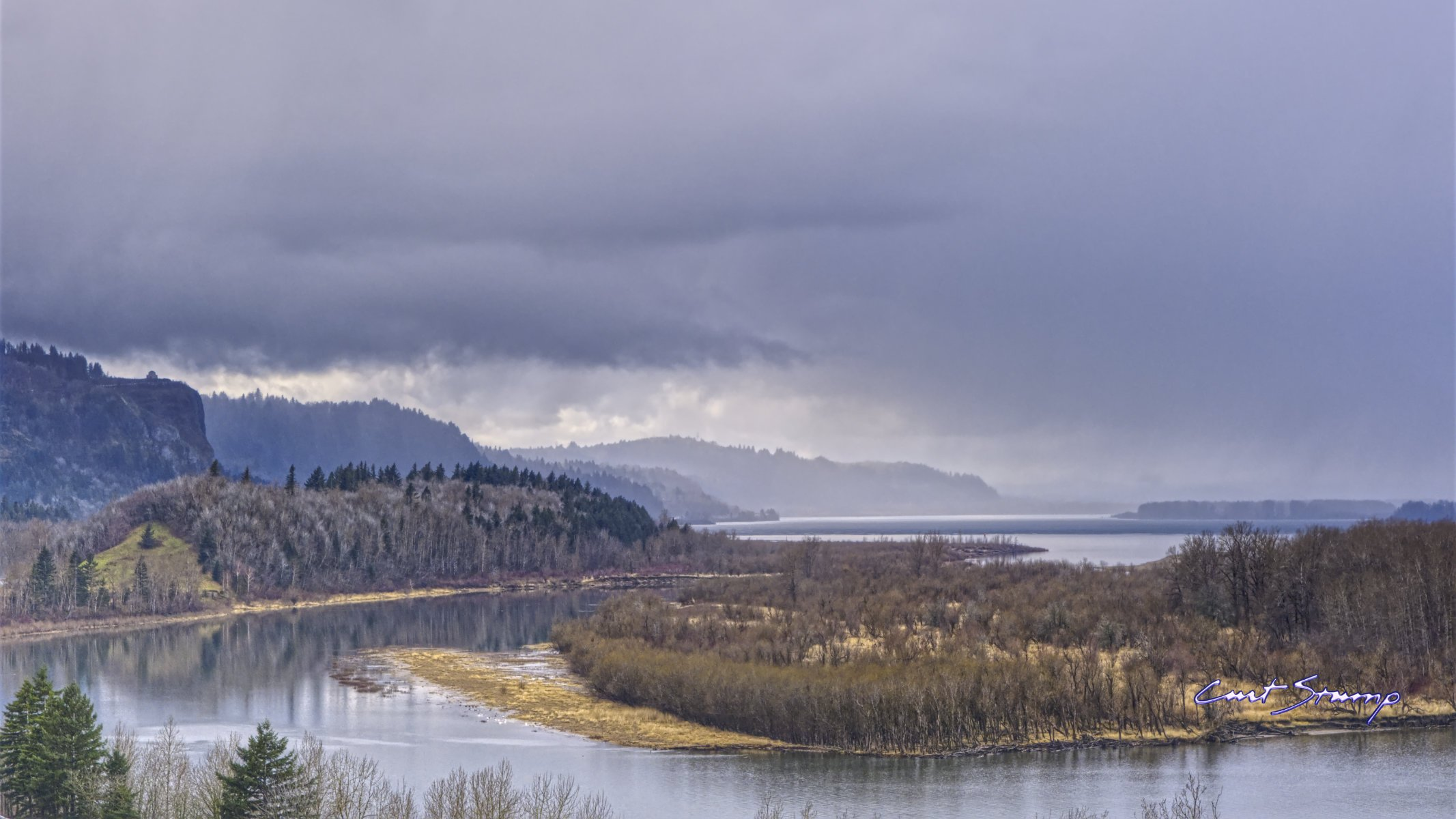 Photo of the Columbia River Gorge near Portland, Oregon. Photo is looking West as the river flows. Island in foreground, rain shower in the distance.