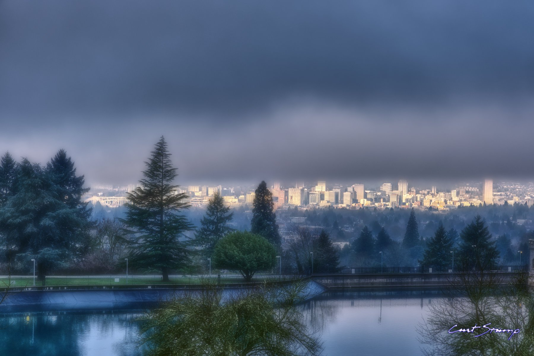 Portland, Oregon, as seen from Mount Tabor park. Dark grey storm clouds and a brightly lit downtown Portland city skyline with buildings. Artificial reservoir and walkway in foreground.