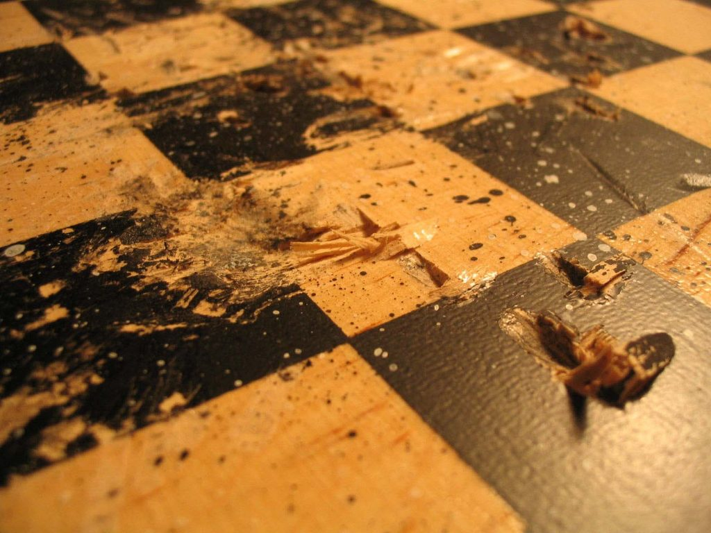 Chess art. This is a chess board that has been damaged by the conflict (the game of chess). The board shows the impact of a battle. This art was made using a hammer to deface the chess board, and splattered paint to represent the loss of chess pieces.