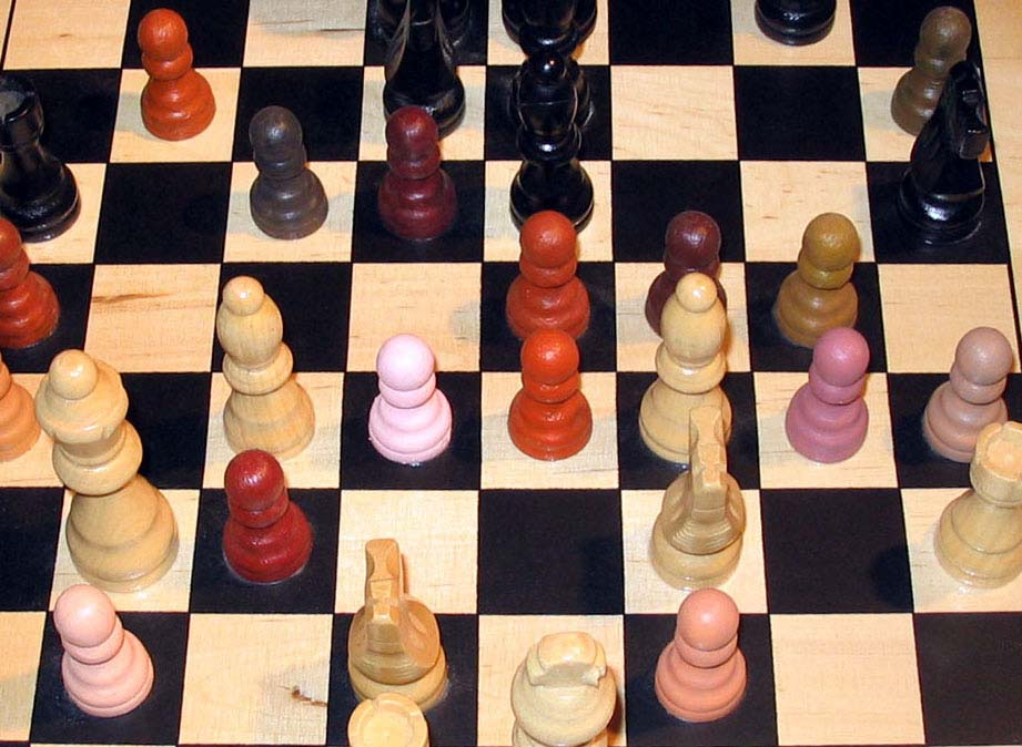 Chess art. This chess board shows pawns painted varying colors and tones representative of flesh (rather than the chess pieces always being black and white).