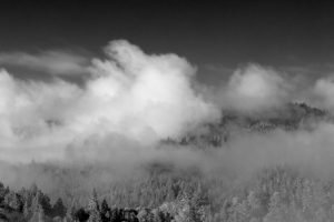 Big puffy cloud settling on a mountain, seen at eye level, black and white photo