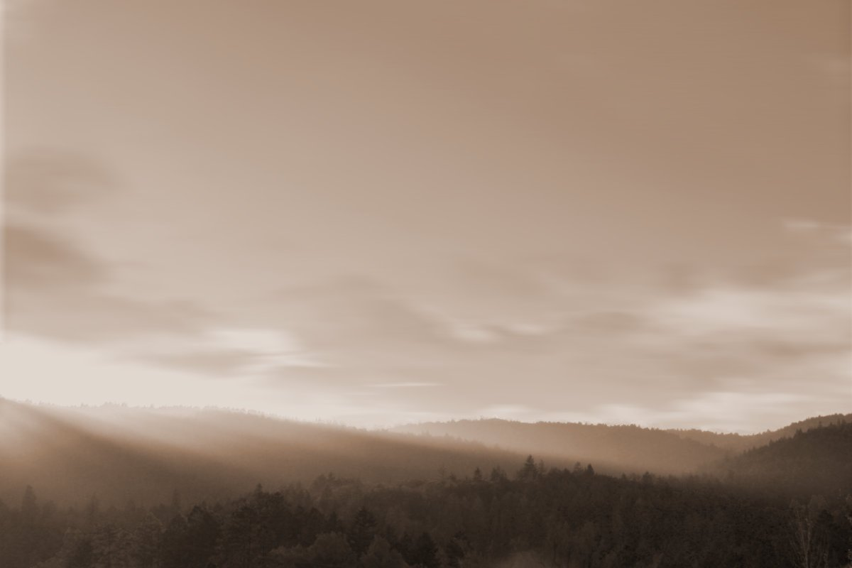 View of a valley with sunlight streaming in from the side. Mystical setting with clouds, sunlight, and valley hills. Sepia color. Location: Mendocino County, California.